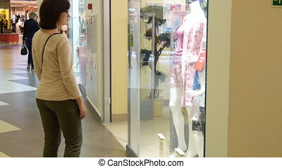 Young woman looking at shop-window in trade center