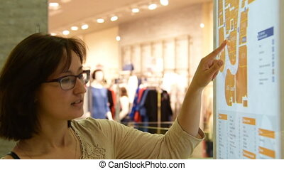 Young woman searching for a shop on map - Young woman in...