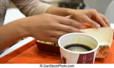 Woman having hamburger and coffee - Fast food dinner....