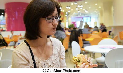 Woman eating hamburger in shopping mall cafe - Young woman...