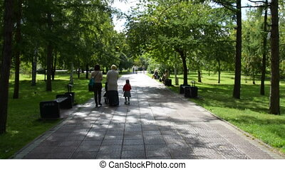 People walking in park on sunny summer day - View to the...