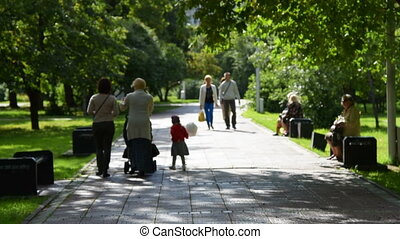 People in green sunny park - People walking along paved...