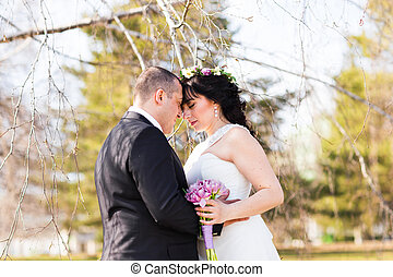 loving groom kissing bride's forehead on wedding walk