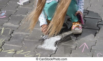 Girl drawing with chalk in the street - Little girl with...