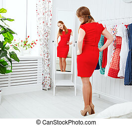 woman in a red dress looks in the mirror and choose clothes...