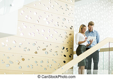Young couple on stairs in the office