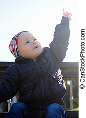 child shows upwards - The little child is pointing upwards...