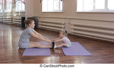 Pregnant woman with her first kid daughter doing gymnastics...