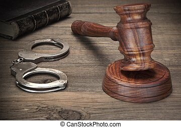 Handcuffs, Judge Gavel And Old Law Books On Wooden Table -...