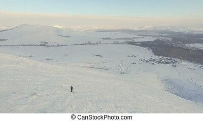 Skier skier begins descent from the summit