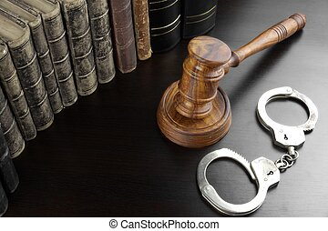 Judges Gavel, Handcuffs And Old Book On The Black Table -...