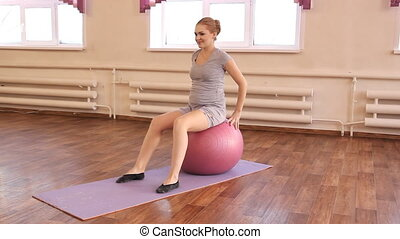 young pregnant woman doing gymnastic - A young pregnant...