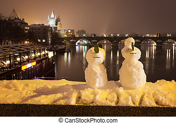Snowmans and Charles Bridge as background, Czech Republic -...