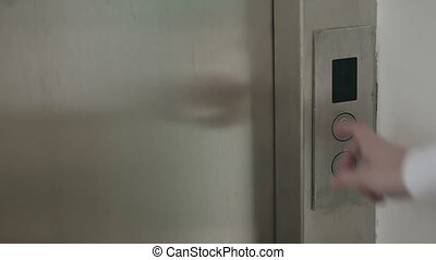 womans hand presses the elevator button - woman's hand...