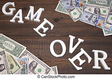Sign Game Over And Dollars Bills On The Wood Background...