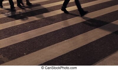 View of crosswalk in night city Feets go on white strips One...
