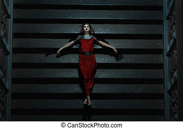 Gothic girl fell on the stairs at night. It is a strange and...