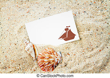 Seashells with blank card on the sand background
