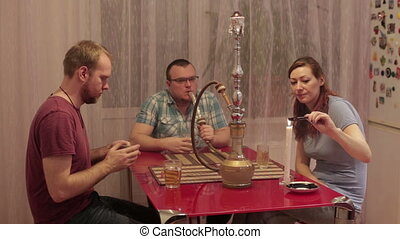 People smoke shisha and playing cards - Two men and a woman...
