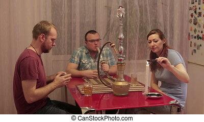 People smoke shisha and playing cards