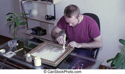 Man restored canvas - A man is sitting at a table covered...