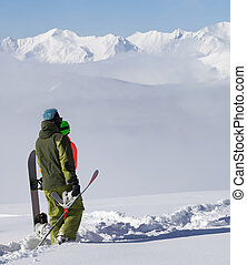 Snowboarders on off-piste slope after snowfall Caucasus...