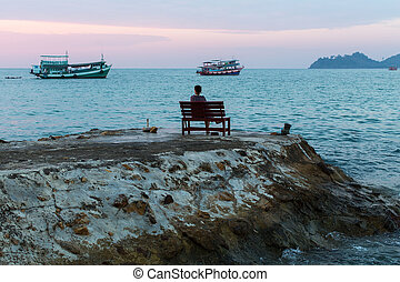 Lonely woman sitting on a bench on a promontory of the sea...