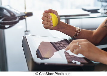 Stressed office worker with anti stress ball types email -...