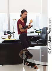 Nervous business woman with anti stress ball holds tablet -...