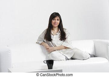 Serene brunette sitting on sofa