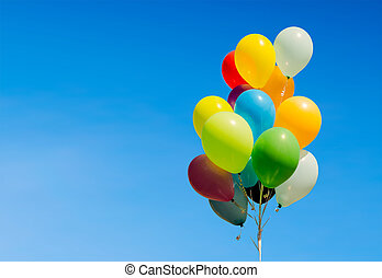 Colorful bunch of helium balloons isolated on background,...