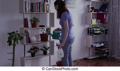 Woman watering flowers with water standing on the shelves...