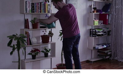 Man watering flowers with water standing on the shelves and...
