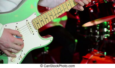 Guitarist play electric guitar on stage. Performance of band.