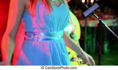 Young blonde girl in blue dress dances on stage. Performance.