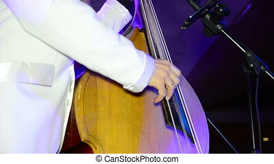 Man plays contrabass on stage. Performance.
