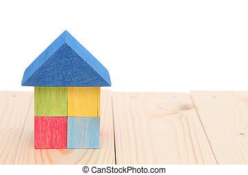 Wooden toy house with colored toy blocks