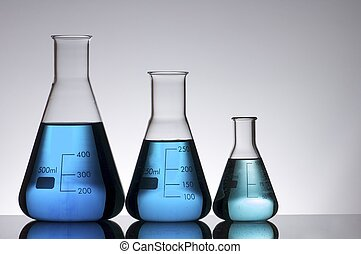 flasks - three conical laboratory flask with blue liquid on...
