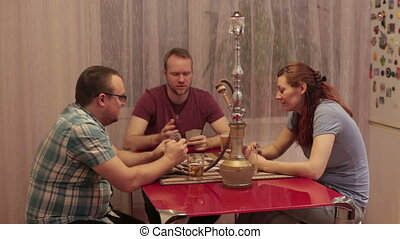 A group of friends are talking and smoking hookah - Two men...
