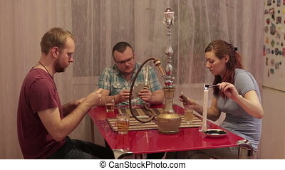 A woman and two men smoking shisha and talking