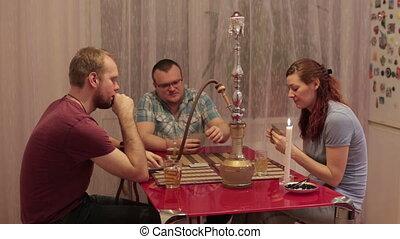 Woman and two men smoking shisha and talking