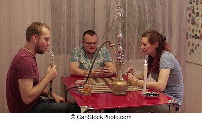 Two men and woman smoking shisha and talking