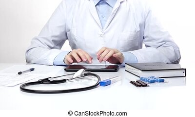 Doctor typing something on the tablet, white - Doctor typing...