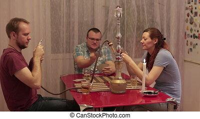 Men and woman smoking shisha and talking - Two men and a...