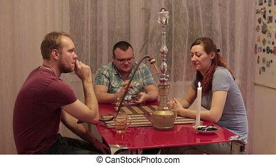 Adult smoking shisha and talking - Two men and a woman...