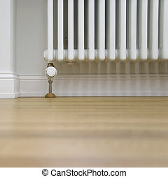 radiator and parquet - radiator with thermostat in a modern...