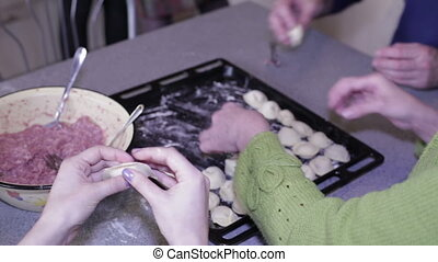 People mold dumplings and put on a baking sheet - Female and...