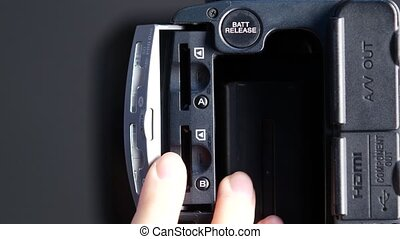 Hand opens flash drive video outputs of camera, close up -...