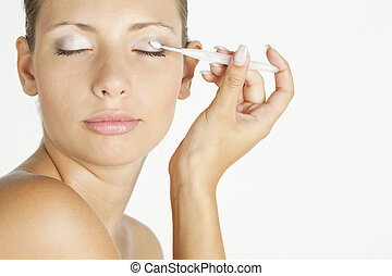 portrait of young woman putting on eye shadows