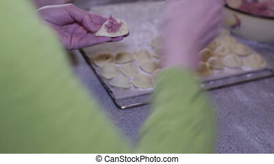 Cook sculpts dumplings - Female hand put the stuffing on the...